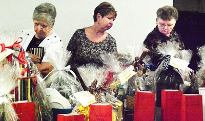 Debbie Blank   The Herald-Tribune Joan Lohrey (from left) and Micki Strohmier, Brookville, and Edith Lecher, Enochsburg, check out Chinese raffle baskets.