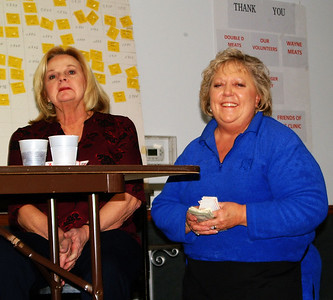 Debbie Blank | The Herald-Tribune Marcy Wurtz (from right), Southeast Indiana Health Center Drawdown Fundraiser creator and coochair; Norma Nobbe and many other volunteers keep the evening moving along. A thank you sign behind them denotes contributors. Former SEIHC nurse practitioner Beverly Metze won the evening's top cash prize, $3,000.