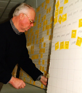 Debbie Blank | The Herald-Tribune Ken Wanstrath was one of several volunteers covering the board with names and numbers already drawn.