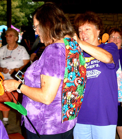Debbie Blank | The Herald-Tribune<br /> Beth Main, Lawrenceburg, pins a superhero cape on Barbara Ankenbauer, Aurora. Both are members of Toon's Platoon, supporting Alzheimer's patient Dan Toon, Guilford.