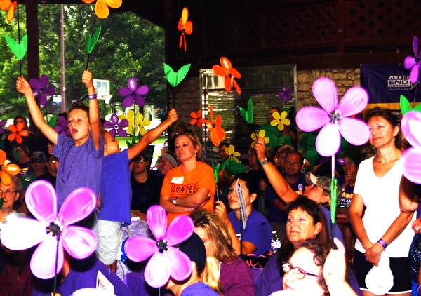 Debbie Blank | The Herald-Tribune<br /> Before the walk began, participants held up flowers signifying the reasons they are raising funds to battle Alzheimer's and related dementias.