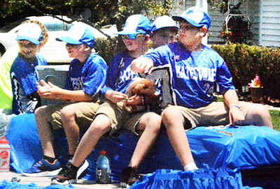 Will Fehlinger | The Herald-Tribune Team members of the Batesville Bats 10-under baseball club pass out candy during the Summerfest parade Saturday afternoon.