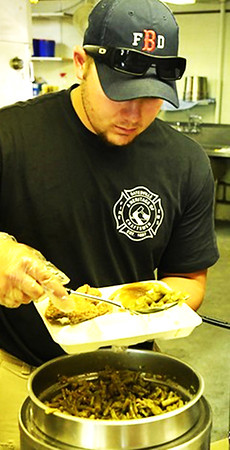Photo courtesy of Rich Fowler | Brush & Palette Frame Shop A Batesville Fire & Rescue member dishes up the traditional fried chicken, green bean and mashed potatoes and gravy feast.