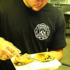 Photo courtesy of Rich Fowler | Brush & Palette Frame Shop<br /> A Batesville Fire & Rescue member dishes up the traditional fried chicken, green bean and mashed potatoes and gravy feast.