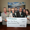 Enterprise Bank contributes $7,500 to Sun Santa Fund. From left, Mark Watson, Enterprise Bank CEO Jack Clancy, Donna Pacelli, Sun Santa co-chair Linda Chemaly, Ian Harmon, co-chair John Chemaly, Erica Getchell, Jackie Silva, and Laurie Bozek. (SUN/Julia Malakie)
