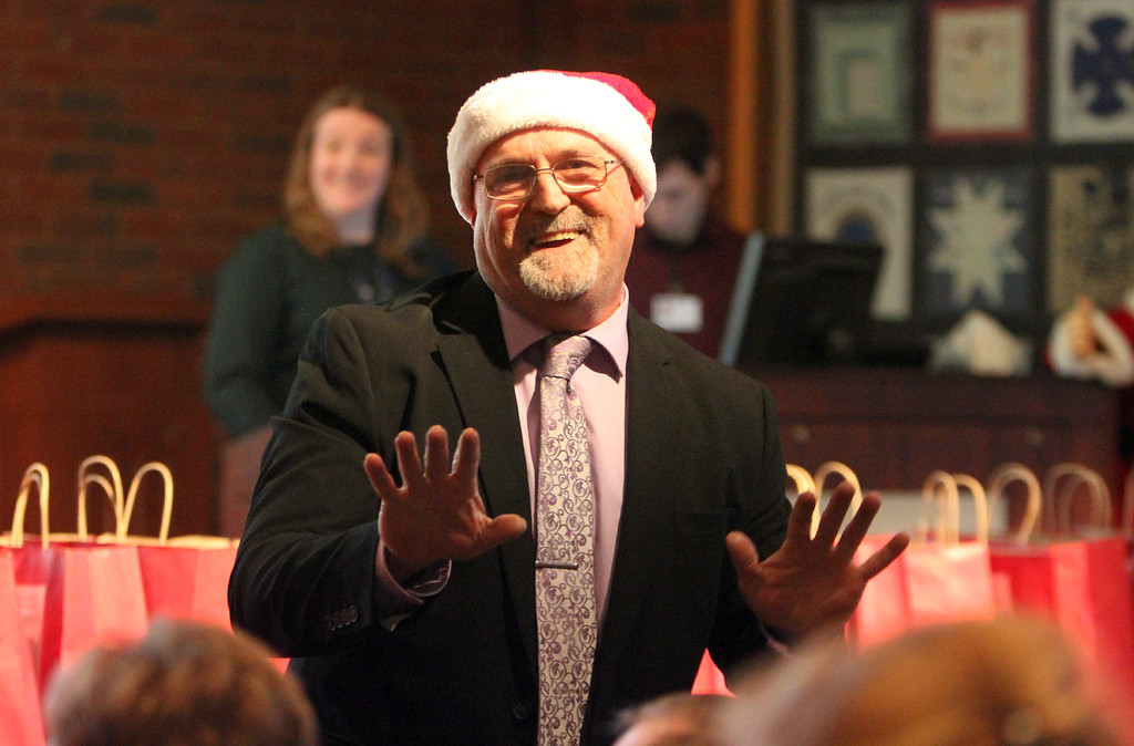 . Paul Beausoleil of Dracut, copy coordinator at LGH, gets people singing Christmas songs before the drawing for the LGH/Sun Santa basket raffle. (SUN/Julia Malakie)