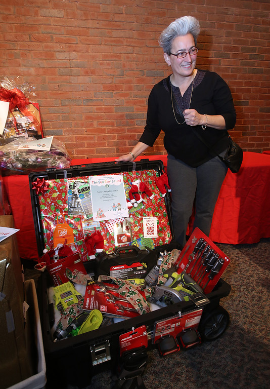 . Janine Daunais of Dracut poses for a photo with what she won at the LGH/Sun Santa basket raffle, Santa\'s Sleigh Repair Kit, with $100 of gift cards, $126 in scratch tickets, and $462 in tools from Home Depot. (SUN/Julia Malakie)