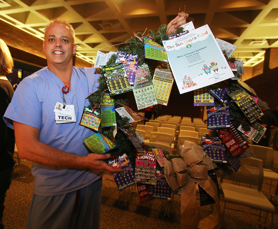 . Emergency Department technician Scott Patnode of Manchester, N.H., picks up what he won in the LGH/Sun Santa basket raffle, Have a Green Christmas Scratch Tickets. (SUN/Julia Malakie)