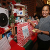 "Raffle tickets for sale at LGH, for Sun Santa baskets put together by Lowell General Hospital departments. Yanina Riley of Lowell, an interpreter at LGH, puts a ticket in the ""Smart Home for the Holidays"" basket. (SUN/Julia Malakie)"