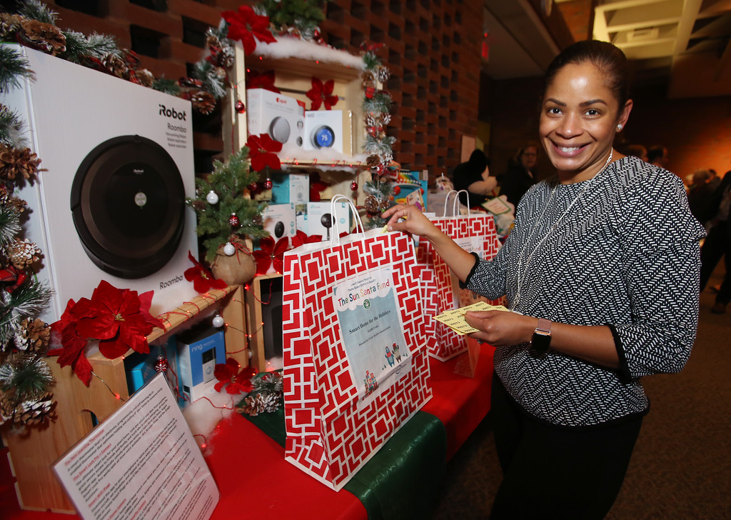 ". Raffle tickets for sale at LGH, for Sun Santa baskets put together by Lowell General Hospital departments. Yanina Riley of Lowell, an interpreter at LGH, puts a ticket in the ""Smart Home for the Holidays\"" basket. (SUN/Julia Malakie)"