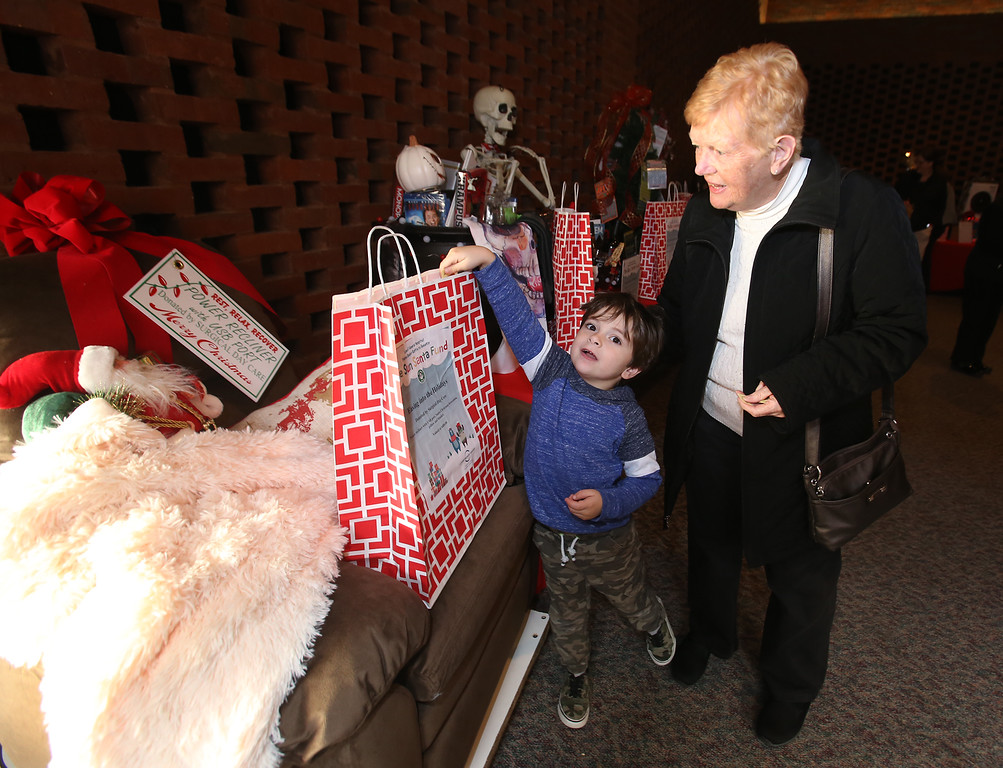 . Raffle tickets for sale at LGH, for Sun Santa baskets put together by Lowell General Hospital departments. Margaret Janas and her great-nephew Kasch Atamian, 4, both of Lowell, look at baskets. (SUN/Julia Malakie)