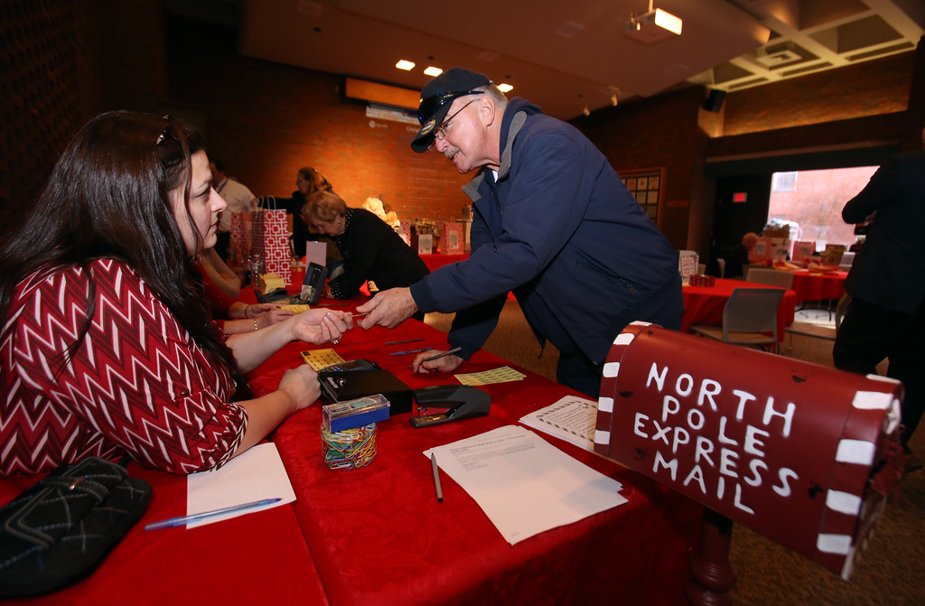 . Raffle tickets for sale at LGH, for Sun Santa baskets put together by Lowell General Hospital departments. Jack Shea of Lowell buys raffle tickets Jessica Field of Dracut, who works in volunteer services at LGH. (SUN/Julia Malakie)