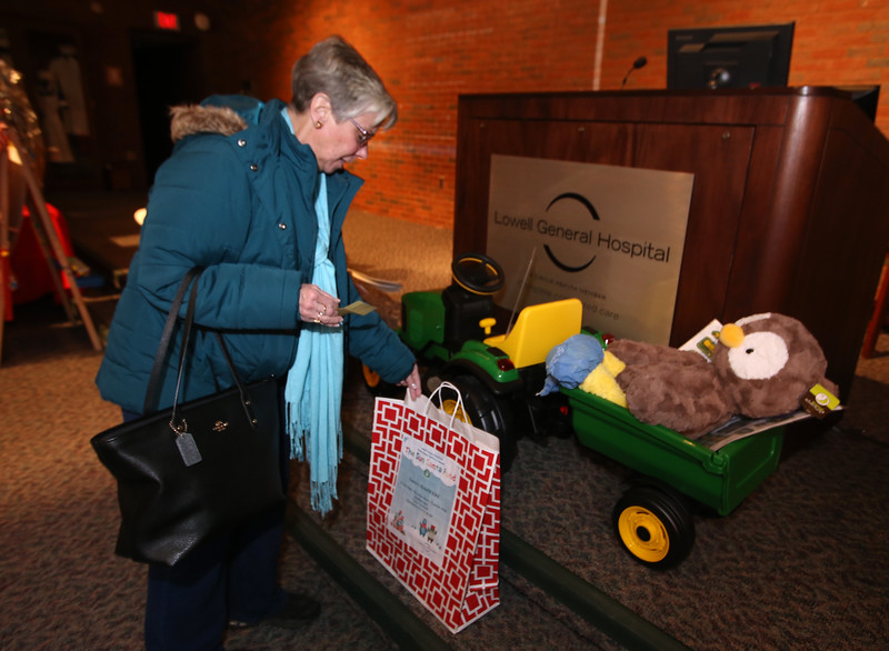 """Raffle tickets for sale at LGH, for Sun Santa baskets put together by Lowell General Hospital departments. Nancy Davis of Billerica puts a ticket in the """"6-Volt Ride On John Deere Tractor with Stuffed Owl"""" basket. (SUN/Julia Malakie)"""
