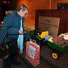 "Raffle tickets for sale at LGH, for Sun Santa baskets put together by Lowell General Hospital departments. Nancy Davis of Billerica puts a ticket in the ""6-Volt Ride On John Deere Tractor with Stuffed Owl"" basket. (SUN/Julia Malakie)"
