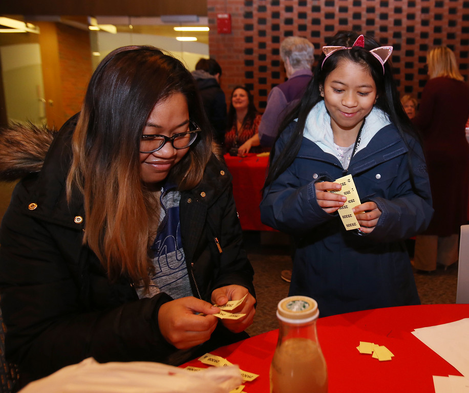 ". Raffle tickets for sale at LGH, for Sun Santa baskets put together by Lowell General Hospital departments. Noeun ""Nina\"" Chhim of Lowell, a CAT scan tech aide at LGH, and her daughter Nadiya Lam, 10, tear their raffle tickets apart. (SUN/Julia Malakie)"