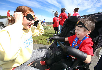 5th annual Middlemiss Big Heart 5K, at Dracut education complex. Alli Weed, 16, of Pelham, N.H., puts on a mask on instructions from Jack Middlemiss, 5, of Dracut, who was dressed as Dash from The Incredibles. (SUN/Julia Malakie)