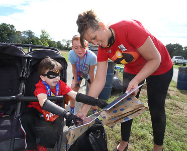 5th annual Middlemiss Big Heart 5K, at Dracut education complex. Kate Middlemiss of Dracut shows son Jack, 5, two superhero drawings that she'd be given for Jack and his sister Grace. At rear is family friend Lexi Weed, 11, of Pelham, N.H.(SUN/Julia Malakie)