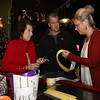 """Steve Panagiotakos, center, with his mother Edna Panagiotakos of Lowell, left, and his wife Christine Panagiotakos, who were preparing raffle ticket bunches, at his annual fundraiser for Sun Santa and """"It's All About the Kids Foundation"""" at the Blue Shamrock. (SUN/Julia Malakie)"""