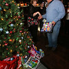 """Steve Panagiotakos' annual fundraiser for Sun Santa and """"It's All About the Kids Foundation"""" at the Blue Shamrock. Anne Sepe of Lowell (Steve's assistant) directs Angelo Karabatsos of Newburyport as he arrives with his present. (SUN/Julia Malakie)"""