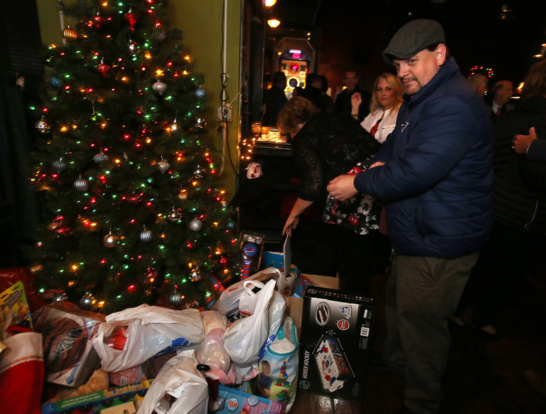 """Sean Callahan of Lowell adds his present to the pile at Steve Panagiotakos' annual fundraiser for Sun Santa and """"It's All About the Kids Foundation"""" at the Blue Shamrock. (SUN/Julia Malakie)"""