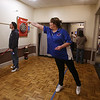 Patriot Dart League's annual tournament/fundraiser for Sun Santa, at the Knickerbocker Club. Donna Lemieux of Dracut throws as her partner in mixed doubles competition, Jason Ogasian of Lynn, watches at right. (SUN/Julia Malakie)