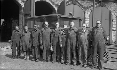 2021.009.02.005--charles stats PC neg [Doc Yungmeyer]--AT&SF--day force employees at roundhouse--Topeka KS--1939 0319. Right to left: John Murphy, hostler; J.E. McGaffin, roundhouse foreman; A.T. Piper, boiler inspection; R.E. Booher, machinist; R.S. Pardee, boiler washer helper; N.R. Pooler, machinist; A.H. Pinkston, wiper; R. Harris, boiler washer; James Brown, boiler washer helper.