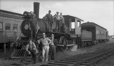 2021.009.02.019A--charles stats PC neg [Doc Yungmeyer]--Ferdinand Railroad--steam locomotive 4-4-0 3 with crew and fans posing--Ferdinand IN--1938 0903. Upper left to right: fireman, engineer, M.C. Poor; lower left to right: D.K. Peterson, V.F. Grewe (Ferdinand general manager), D.W. Yungmeyer.