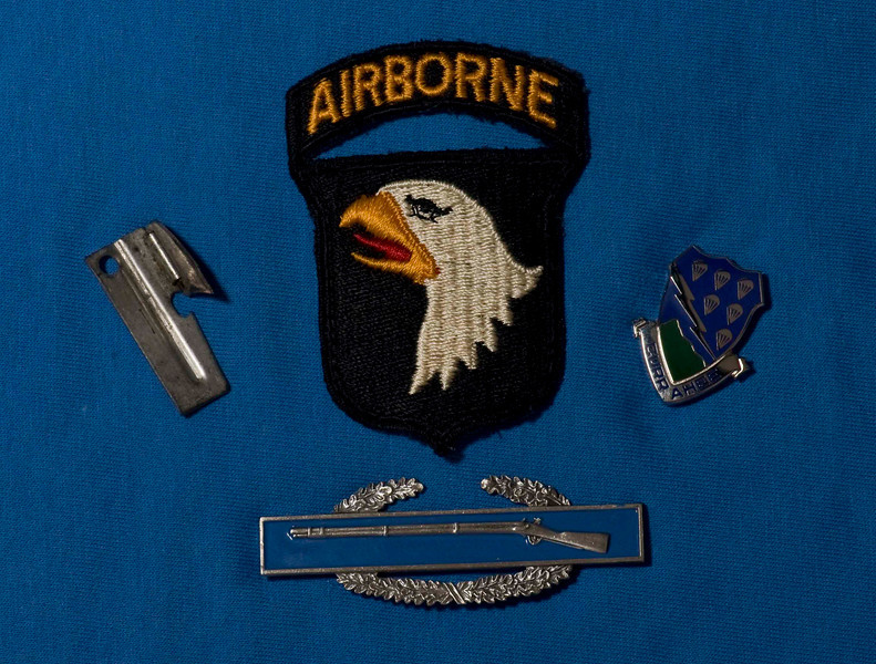 The patch, a P-38 for opening C-rations, the battalion crest and a Combat Infantryman's Badge (earned by most infantrymen in Charlie Company).
