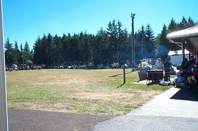 Plenty of tents and bikes on this grassy field with salmon cooking on the BBQ.