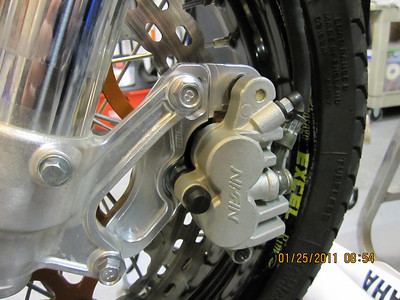 The front brake is a mixed bag of components including a Braking caliper relo bracket, MotoMaster 320 m.m. full floating race rotor, and O.E.M. caliper.  Soon to have a steel braided brake line.