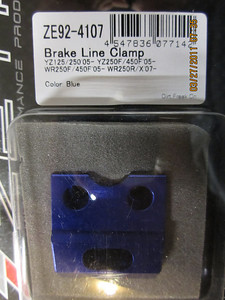 Zeta front brake line clamp.  This was necessary for the new steel line and routing of the front brake line when running the 320 m.m. rotor.  The stock brake line clamp has a curve in it to accomadate running the line on the inside of the fork leg.  In SuMo trim it will run on the outside of the left fork leg.