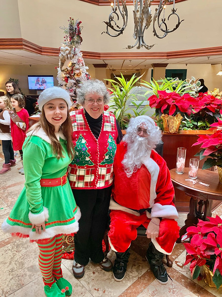 Santa's elf, Tessa Fowler of Billerica, and Westford Family Funfest Chairwoman Patti Mason of Westford with Santa at the Regency