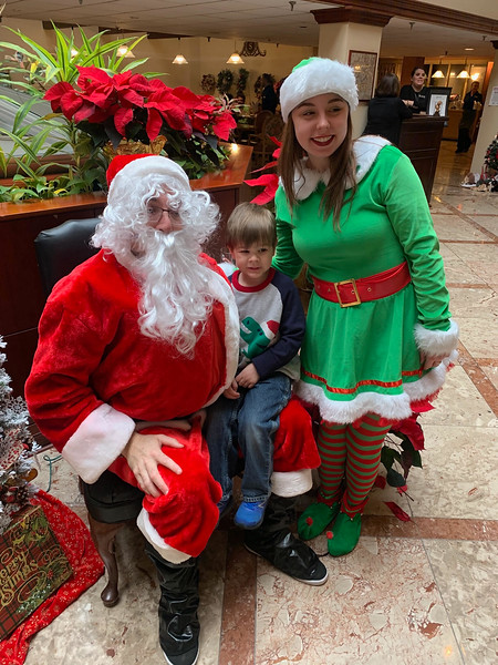 Declan Shields of Westford tells Santa and his elf, Tessa Fowler, of Billerica what he wants at the Regency.