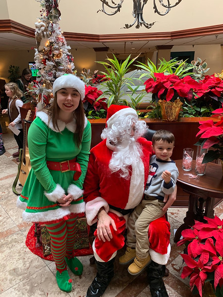 Santa and one of his elves, Tessa Fowler of Billerica, with Benjamin Therriault of Westford at the Regency