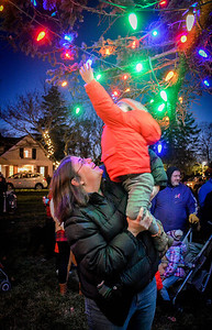 Danielle Okuda of Chelmsford lifts her son, Beckett, 2, to touch the lights hung from the tree that was lit at the Holiday Prelude. SUN/Caley McGuane