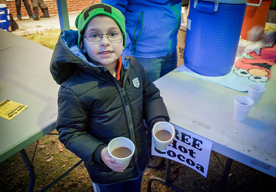 Alden Finkel, 6, of Chelmsford hands out free hot cocoa from his Cub Scout Pack 45 stand at the Holiday Prelude in Chelmsford. SUN/Caley McGuane