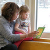 Kathy Twombly of Chelmsford and her granddaughter Molly Dickieson, 2, of Lowell enjoy a good book at the Chelmsford Public Library on Friday afternoon.  SUN/JOHN LOVE