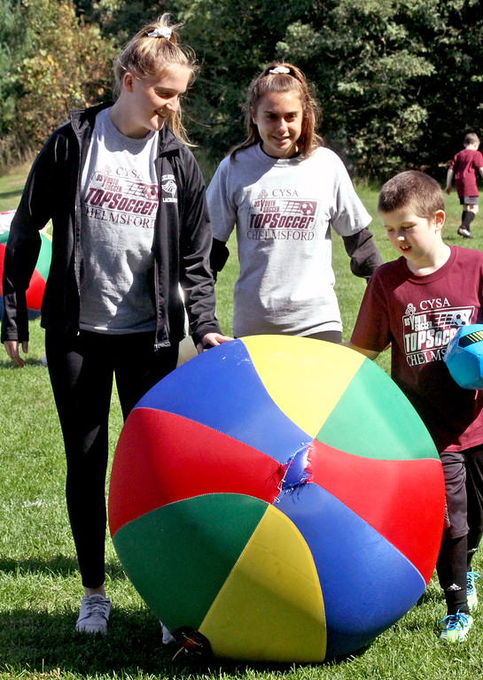 . Rolling out a large soccer ball are volunteers and members of the CHS girls varsey soccer team, L-R, Kathryn Slattery 15, Erin Johnson 15 and with athlete Braydon Blanchard 8 all from Chelmsford. SUN/David H. Brow