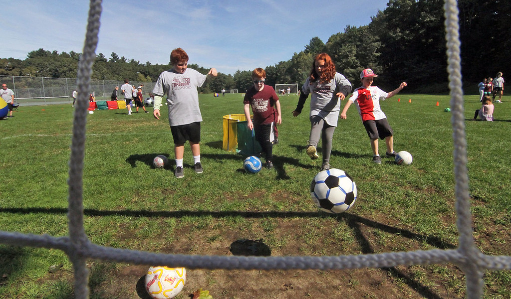 . Volunteers and special needs athletes doing drills at Top Soccer camp in Chelmsford. SUN/David H. Brow