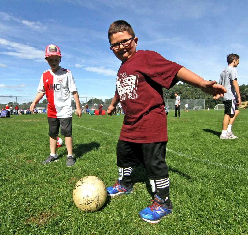 . Having fun and doing drills at the Top Soccer camp at the South Row School in Chelmsford is L-R,  Volunteer Jacob Berry 12, and special needs athlete Connor Murphy 5. SUN/David H. Brow