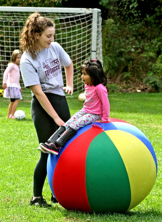 . Volunteer Lisa Macedo 16, works with Alisha Joshi 3 1/2 at the Top Soccer camp. SUN/David H. Brow