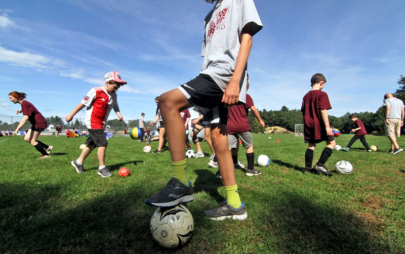 Special needs athletes and volunteers having fun and doing drills at Top Soccer camp at the South Row School in Chelmsford. SUN/David H. Brow