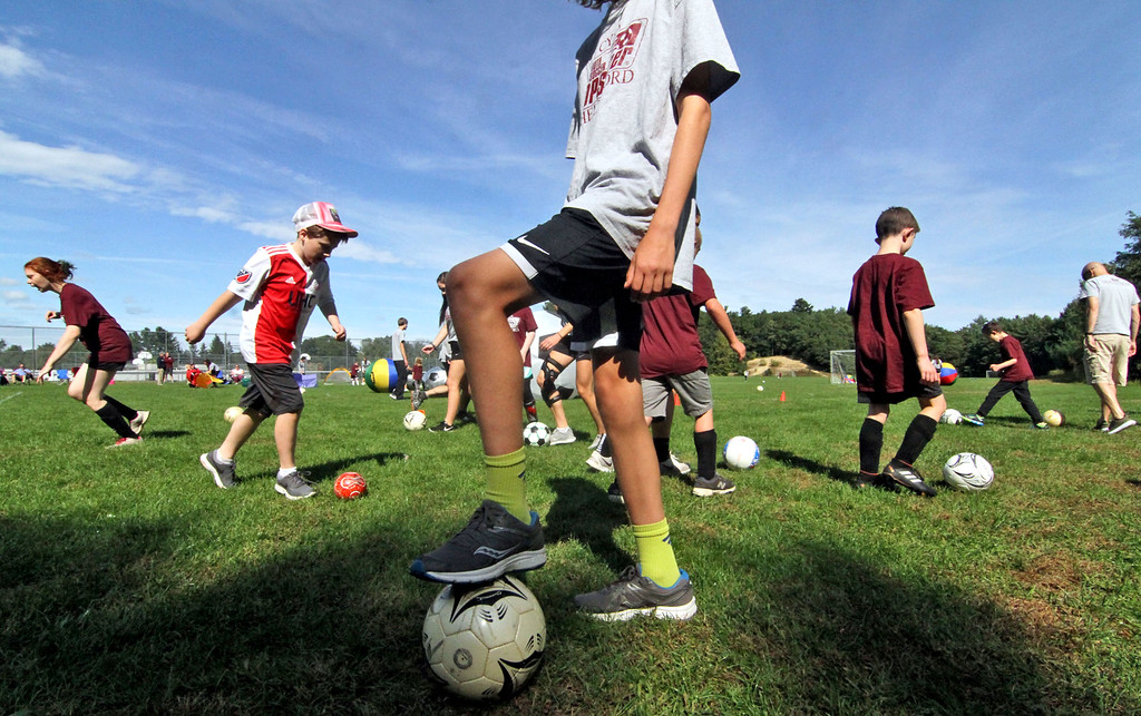 . Special needs athletes and volunteers having fun and doing drills at Top Soccer camp at the South Row School in Chelmsford. SUN/David H. Brow
