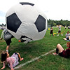 Volunteers and special needs athletes playng crab soccer with a huge soccer ball at the Top Soccer camp. SUN/David H. Brow