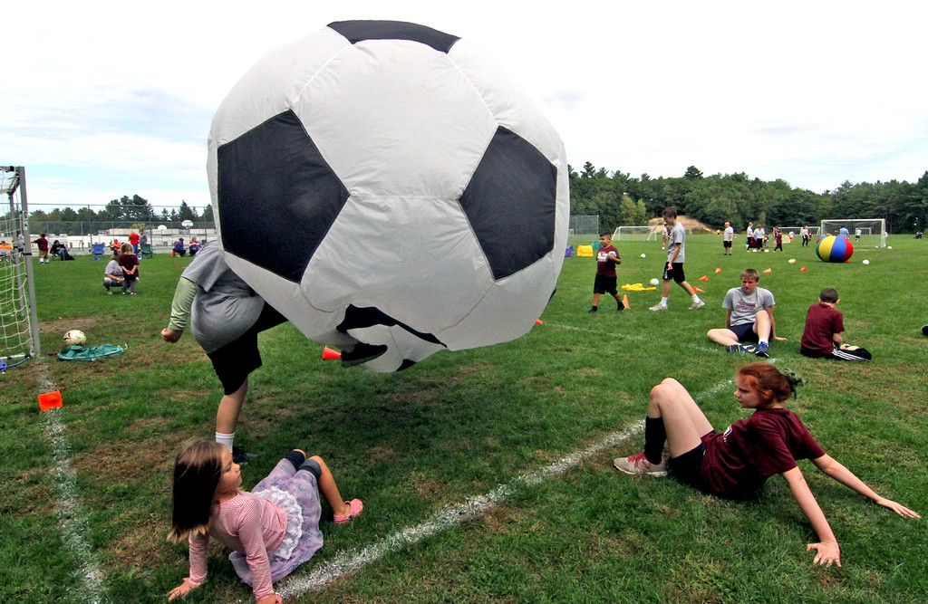 . Volunteers and special needs athletes playng crab soccer with a huge soccer ball at the Top Soccer camp. SUN/David H. Brow