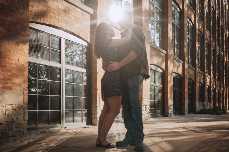 Couple smiles and embraces amidst a refracted star shaped beam of light reflected from the building behind them.