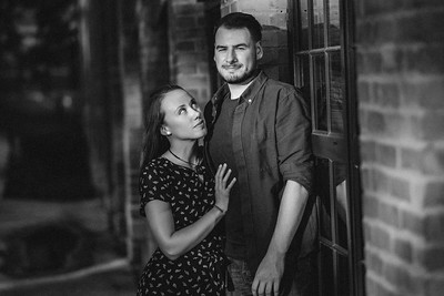 A woman looks up at her fiance standing next to a brick wall as a beam of light illuminates their faces.