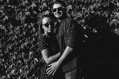 A couple wearing sunglasses smiles into the camera as the sun shines on them in front of an ivy covered wall.