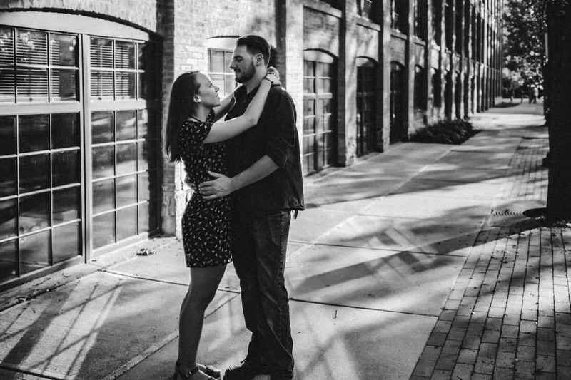 Couple smiles and embraces amidst geometric patterns of light reflected from the building behind them.