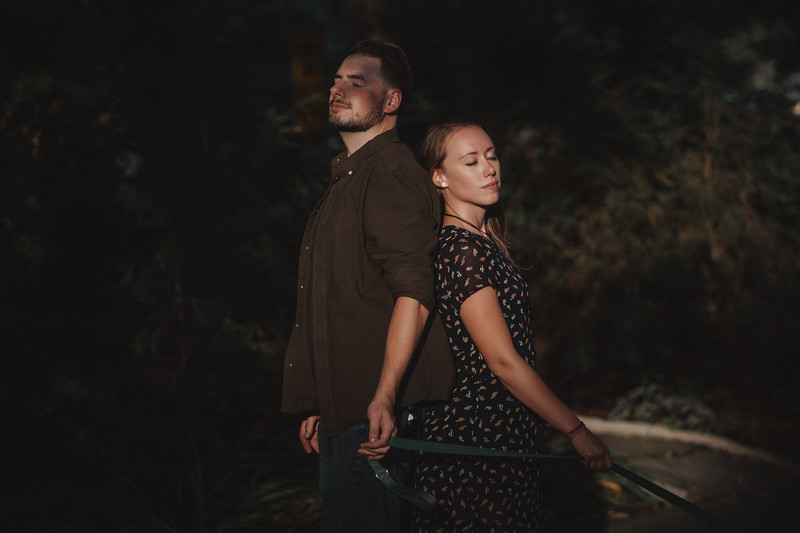 A couple stands back to back with eyes closed in a beam of sunlight amidst lush foliage.